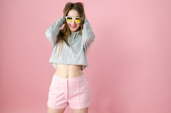 Portrait of young attractive funny teenager girl with straight blonde hair and sunglasses in trendy clothes on the pink background, studio shooting