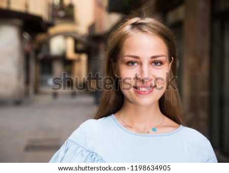 Portrait of young attractive girl in lightweight blue dress walking in historical center of Barcelona