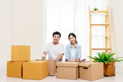 Portrait of young attractive happy asian couple man and woman sitting at new home smiling to camera with carton package box storage to move in empty house. Young married asian relocating home concept.