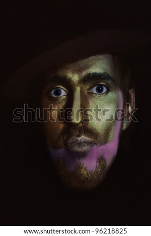 portrait of young attractive man in hat with bronze makeup on her face on black background