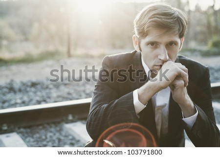 Portrait of young attractive man sitting in railway