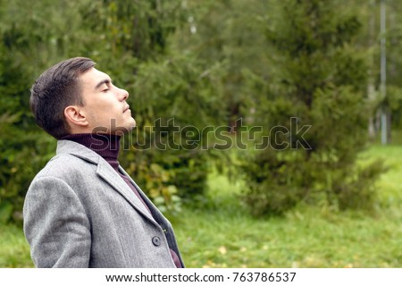 Portrait of young attractive man with a grey coat, breathing in the fresh autumn air in the Park, showing his face to the wind. The concept of freedom, ecology, life without borders.