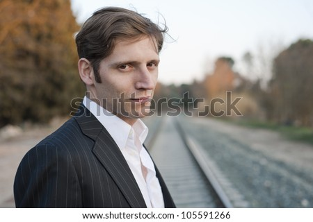Portrait of young attractive man with suit in rail way
