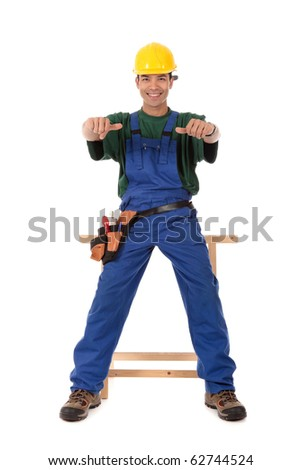 Portrait of young attractive Nepalese carpenter with thumbs-up, wearing a blue overall, tool belt and helmet, sitting and smiling . Studio shot. White background.