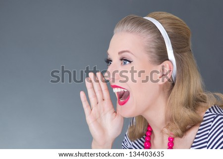 portrait of young attractive pinup girl screaming over grey