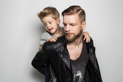 Portrait of young attractive smiling father playing with his little cute son. Fathers day.  Studio portrait over white background