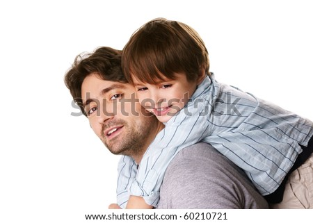 Portrait of young attractive smiling man playing with his little cute son on white background