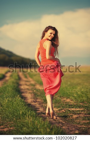 Portrait of young attractive smiling woman walking on the road outdoor in summer