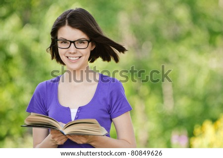 Portrait of young attractive smiling woman wearing violet blouse and eyeglasses standing at summer green park.