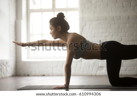 Portrait of young attractive sporty fit lady warming up, practicing yoga, doing Bird dog exercise, Donkey Kick pose, working out, wearing sportswear, closeup, white loft studio background, side view