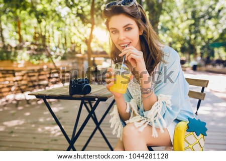 portrait of young attractive stylish woman sitting in cafe, smiling, looking in camera, drinking juice smoothy, healthy lifestyle, street boho style, fashionable accessories, vegetarian, fruit diet