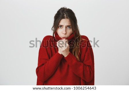Portrait of young attractive stylish woman with brown hair in red winter sweater freezing, warming up hands over white background. Cute student feels cold as she ran from office to buy cup of coffee.