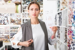 Portrait of young attractive woman choosing buttons for clothes in needlecraft store..