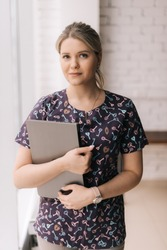 Portrait of young attractive woman wearing casual clothing holding folders while standing in light office room near window, looking at the camera.