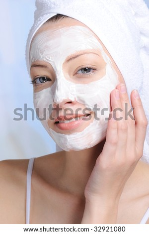 portrait of young attractive woman with cosmetic mask on her face