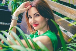 Portrait of young attractive woman with red hair and bright red lips in green short sleeve blouse. Woman is sitting on wooden bench among green plants and smiling. Selective soft focus, toned image