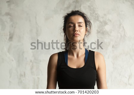 Photo of Portrait of young attractive yogi woman with her eyes closed in meditating pose, relaxation exercise, working out, wearing sportswear, black top, indoor close up image, wall background