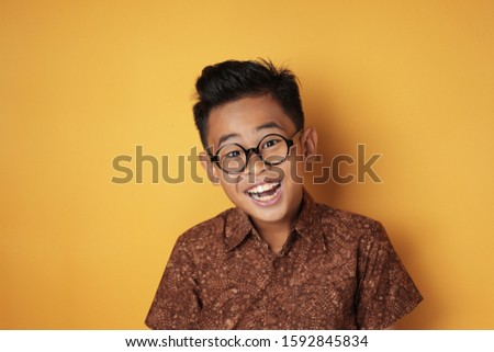 Portrait of young aute Asian boy wearing eyeglasses and batik shirt looking at camera and laugh, against yellow background Stock fotó ©