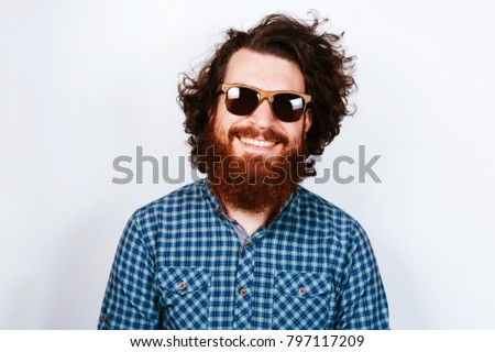Portrait of young bearded hipster man wearing sunglasses. Happy concept. Smiling man with beard. Curly hair.