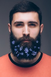 Portrait of young bearded hipster man with flowers in his beard standing against grey background