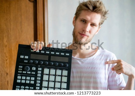 portrait of young bearded man sound producer  holding midi controller and headphones #1213773223