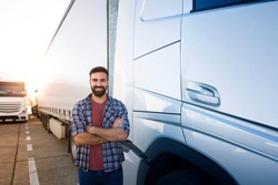 Portrait of young bearded man standing by his truck. Professional truck driver with crossed arms standing by semi truck vehicle.