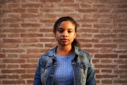 Portrait of young beautiful African American woman looking at camera with serious face outdoors. Serious millennial girl standing in front of a brick wall. People and emotions concept.