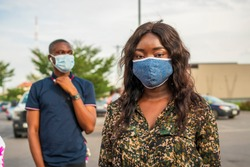 portrait of young beautiful African woman in queue wearing homemade mask for protection with a black man blurred in background observing social distancing-focus on woman on right