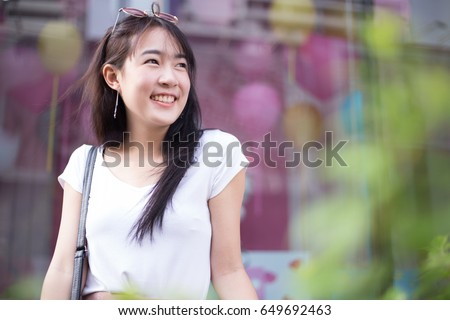 Portrait of young beautiful and pretty Asian woman with perfect smiling looking outside or looking to some people in the green garden city