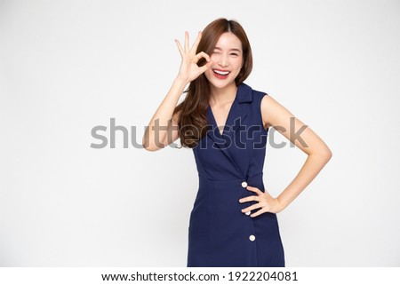 Portrait of Young beautiful Asian businesswoman smiling and showing ok sign on hand isolated on white background, Looking at camera Stock photo ©