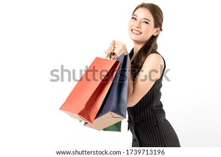 Portrait of young beautiful asian girl wearing black dress holding shopping bags and smile isolated over white background. Online shopping and black friday concept.