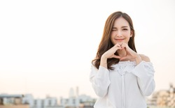 Portrait of young beautiful asian woman hands gesture in heart shape on city sky roof top. Smile face asian lady girl wear casual cloth. Japanese girl lifestyle, lovely woman valentines' day concept