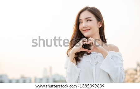 Portrait of young beautiful asian woman hands gesture in heart shape on city sky roof top. Smile face asian girl wear casual cloth. Japanese girl asia lifestyle, love valentines' day concept