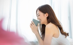 Portrait of young beautiful asian woman hands holding coffee cup morning spring time in white bedroom. Happy cheerful relaxing in summer. Korean makeup wakeup university asia lifestyle concept.