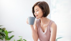 Portrait of young beautiful asian woman hands holding coffee cup morning spring time in white bedroom. Happy cheerful relaxing in summer. Korean makeup wakeup university asia lifestyle concept