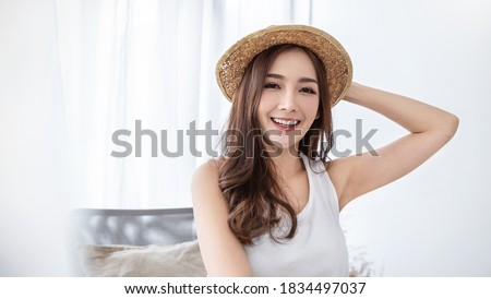 Portrait of young beautiful asian woman on holiday vacation summer time in white bedroom. Happy cheerful girl in summer. Korean makeup under arm skincare. University woman fashion lifestyle concept.