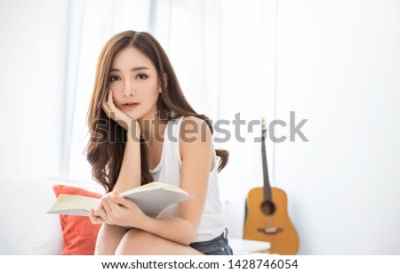 Portrait of young beautiful asian woman relax holding book in bedroom with copyspace. Smile happy asian girl relaxing knowledge education university lifestyle, back to school concept