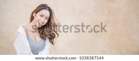 Portrait of young beautiful asian woman sit and relax over vintage wall. Smile happy asian girl looking. Lifestyle people beauty girl next door concept banner