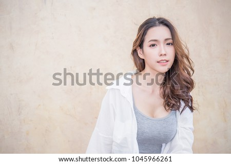 Portrait of young beautiful asian woman sit and relax over vintage wall. Smile happy asian girl looking. Lifestyle people beauty girl next door concept.
