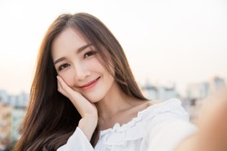 Portrait of young beautiful asian woman  using smart phone selfie live in roof top. Happy asian girl online influencer blogger. Education technology connected asia people, woman lifestyle concept