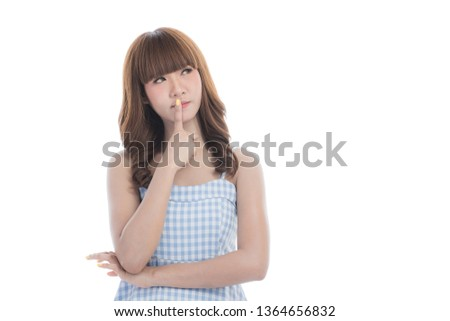 Portrait of young beautiful Asian woman with brace retainers with dark brown hair in light blue checked dress smiling and pointing at right copy space on isolated white background