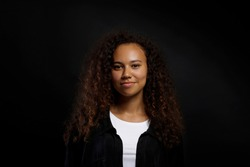 Portrait of young beautiful black woman standing in the dark showing emotions. Female with emotional facial expression over black wall background. Close up, copy space.