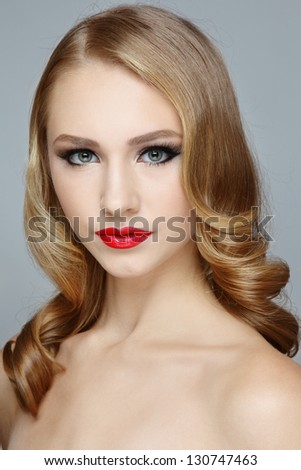 Portrait of young beautiful blond girl with red lipstick and stylish hairdo