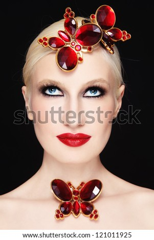 Portrait of young beautiful blond girl with stylish make-up and red plastic butterflies