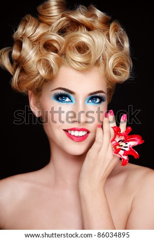 Portrait of young beautiful blond woman with fancy make-up and hairstyle
