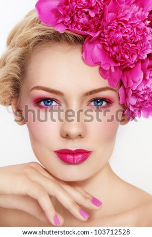 Portrait of young beautiful blond woman with stylish pink make-up and peonies in her hair