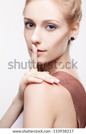 portrait of young beautiful blonde woman asking to be quiet