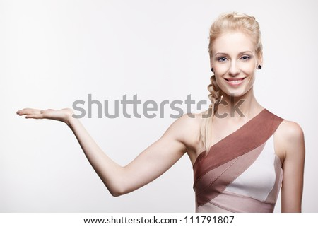 portrait of young beautiful blonde woman posing with empty hand palm up,  holding small imaginary object