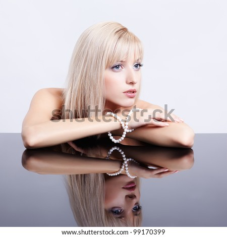portrait of young beautiful blonde woman sitting with string of pearls at reflecting table