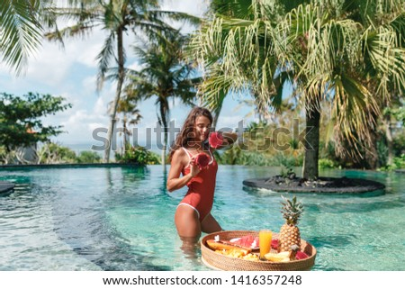 Portrait of young beautiful brunette girl in red  swimsuit with dragon fruits and beakfast tray in the pool. Sexy model with cute smile posing near swimming pool in hotel.Vegetarian and healthy  #1416357248